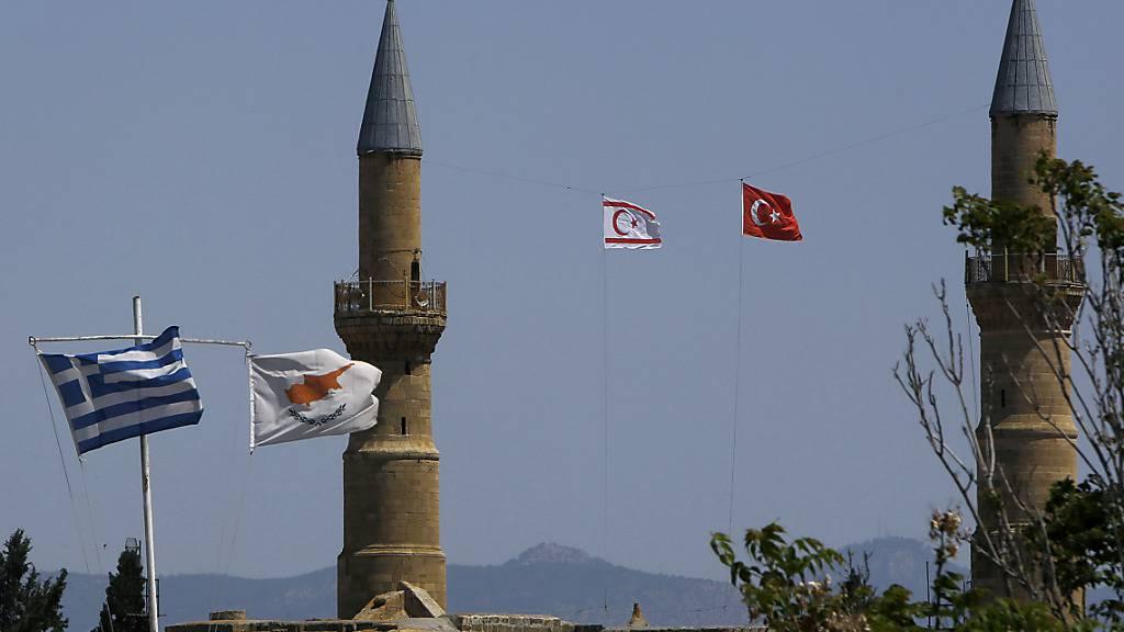 Griechische und zypriotische Flaggen flattern im Wind im südlichen Teil. Währenddessen im Norden, im türkisch besetzten Gebiet, eine türkische und eine türkisch-zypriotische Flagge auf einem Minarett der Selimiye-Moschee in der geteilten Hauptstadt Zyperns wehen. Foto: Petros Karadjias/AP/dpa