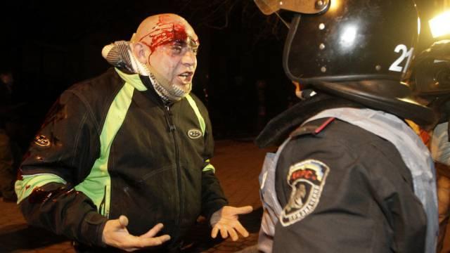 Verletzter Demonstrant in Kiew schreit einen Polizisten an