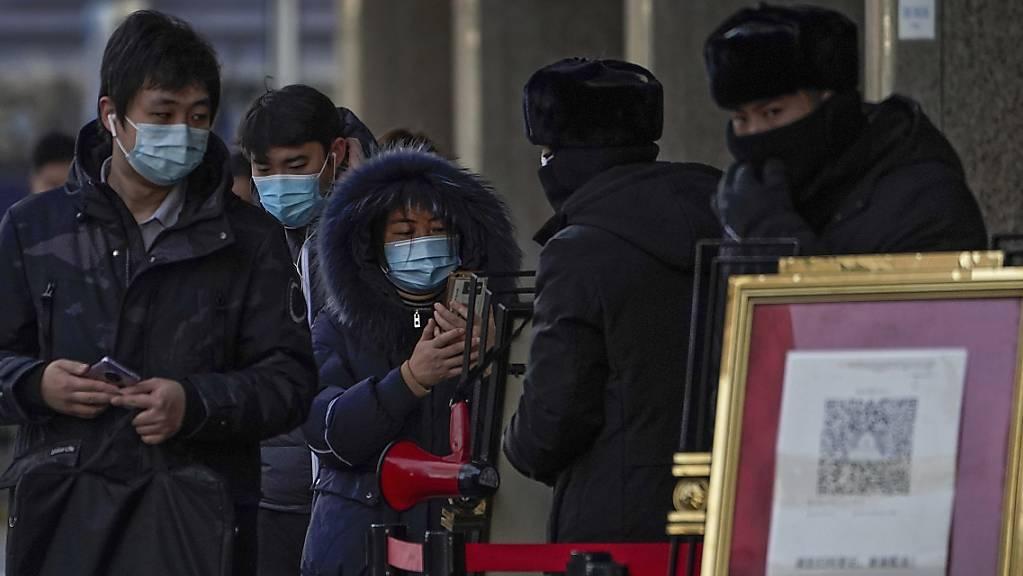 Menschen, die Gesichtsmasken tragen, scannen mit ihren Smartphones einen Code, bevor sie ein Bürogebäude betreten.