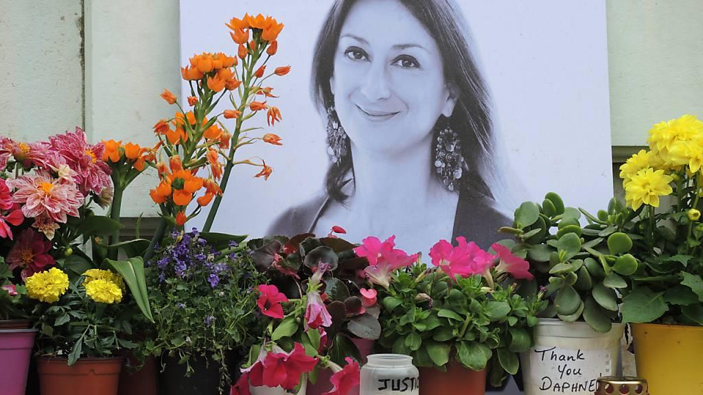 ARCHIV - Kerzen und Blumen stehen in Valletta vor einem Foto der ermordeten maltesischen Journalistin Daphne Caruana Galizia. Foto: Lena Klimkeit/dpa