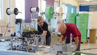 Warum werden die Ohrenbändel nicht angeklebt? Felix Schönle (rechts) justiert mit Produktionsleiter André Sägesser die neue Maschine.