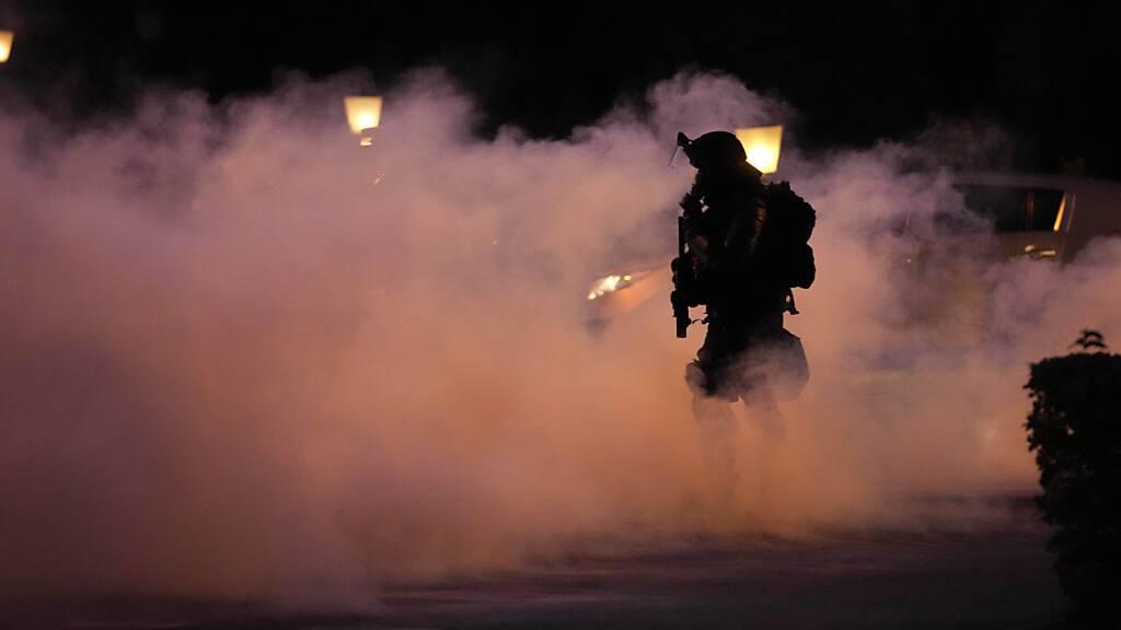 Ein Polizist geht durch Rauch während einer Demonstration gegen die Corona-Impfungen und weiteren Maßnahmen zur Eindämmung der Pandemie. Foto: Petr David Josek/AP/dpa