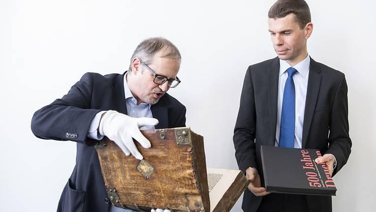 Ein gewichtiges Stück Geschichte: Historiker Adrian Scherrer (links) begutachtet die etwa fünf Kilo schwere Zwingli-Bibel mit Orell-Füssli-CEO Martin Buyle.
