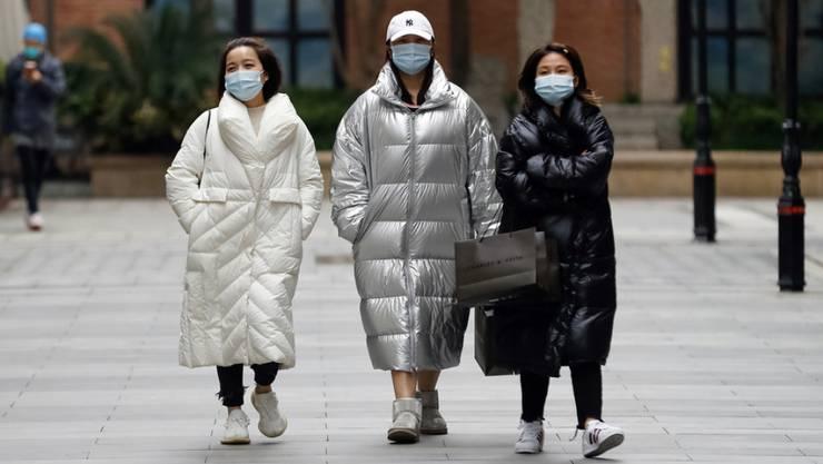 Passanten am Montag in Wuhan, wo die Pandemie ihren Ausgang nahm. Auch Experten fragen sich, warum die Corona-Zahlen aus China eher niedrig sind.