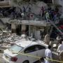 Rettungskräfte und Helfer suchen nach Überlebenden inmitten der Trümmer eines nach einer Explosion beschädigten Gebäudes.