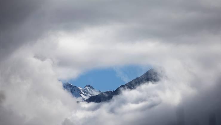 Winterboten in Meiringen im Berner Oberland. Ein Nebelloch gibt die Sicht auf die beschneiten Berge frei.