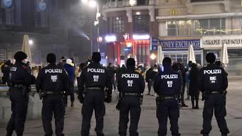 Polizeibeamte beobachten in der Innenstadt das Geschehen in der Silvesternacht. In Österreich galten verschärfte Ausgangsbeschränkungen. Foto: Hans Punz/APA/dpa