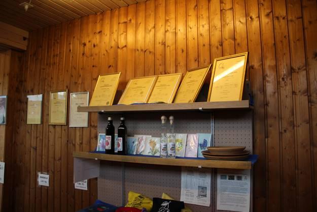 Sieben Gold- und eine Silbermedaille zieren eine Wand im Verkaufsladen