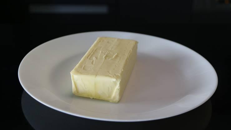 Holt die harte Butter aus dem Kühlschrank und legt sie auf einen Teller. Der Teller sollte genügend gross sein, damit die Schüssel gut kopfüber auf den Teller gestellt werden kann.