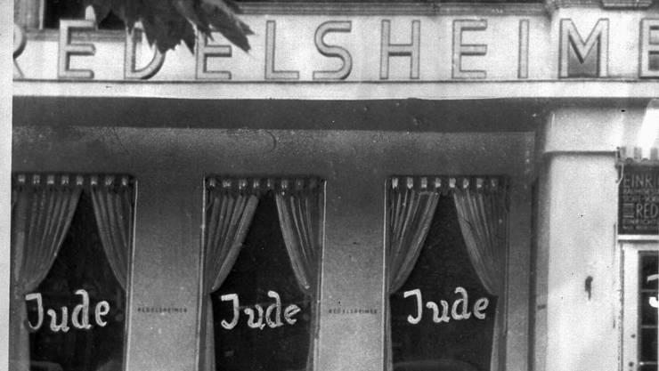 Das Wort Jude ist am 19. Juni 1938 auf die Fensterscheiben eines jüdischen Geschäftes in Berlin geschmiert.