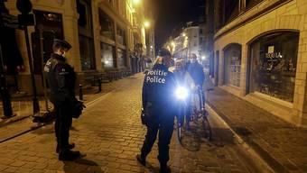 Zwei Polizeibeamte patrouillieren zu Beginn der Ausgangssperre durch die Stadt. Die belgische Regierung führte strengere Maßnahmen ein, um das Risiko der Ausbreitung von Covid-19 zu verringern, da die Zahl der Covid-19-Infektionen stark ansteigt. Foto: Thierry Roge/BELGA/dpa