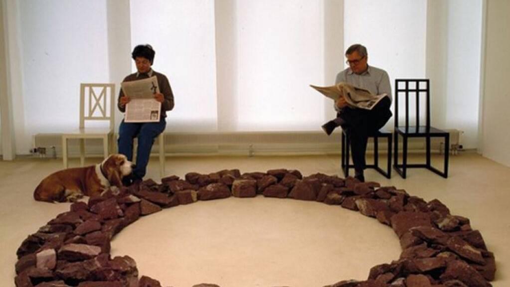 Das Zuger Sammlerehepaar Christine und Peter Kamm auf Stühlen von Josef Hoffmann und der Wiener Avantgarde vor dem Kunstwerk Red Stone Ring von Richard Long. Mit dabei ist der Hund Sir Gordon.