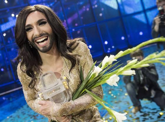 Conchita Wurst mit Blumen und Pokal