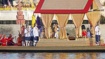 Thailands König Maha Vajiralongkorn lässt sich in Begleitung seiner Frau, Königin Suthida, auf einer goldenen Gondel über den Fluss Chao Phraya rudern.