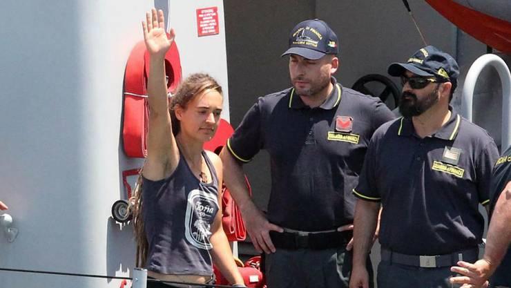 Kapitänin Carola Rackete (Mitte) winkt bei ihrer Ankunft im Hafen von Porto Empedocle. Eskortiert wird sie von der Polizei.