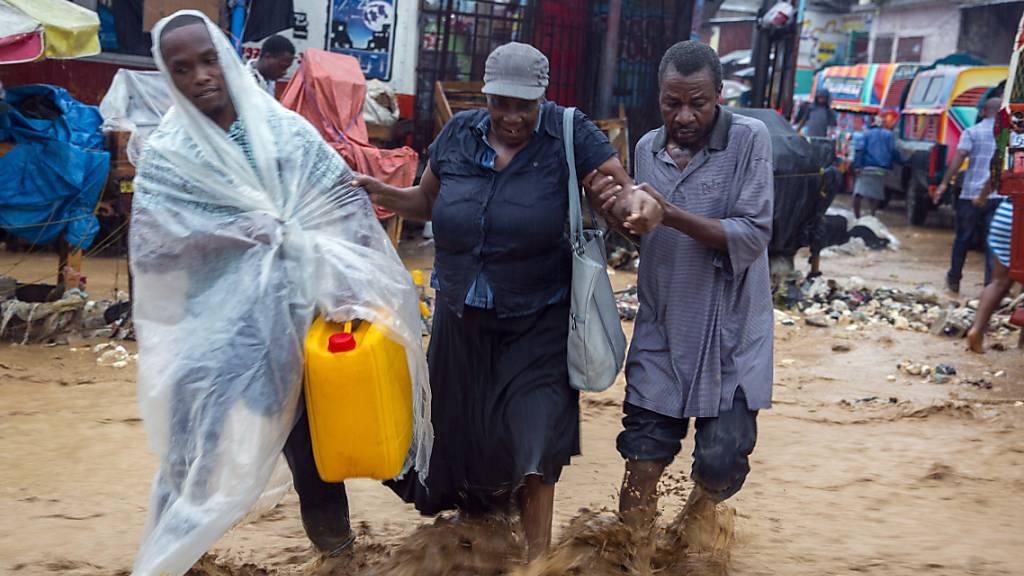dpatopbilder - Menschen gehen während des Tropensturms «Laura» über eine überschwemmte Straße in Haitis Hauptstadt Port-au-Prince. Foto: Dieu Nalio Chery/AP/dpa