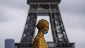 Eine goldene Statue am Pariser Platz Trocadéro trägt eine Schutzmaske. Im Hintergrund ist das berühmte Wahrzeichen Eiffelturm zu sehen. (Archivbild)