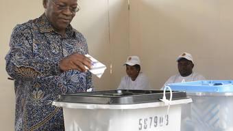 John Magufuli, amtierender Präsident von Tansania und Präsidentschaftskandidat bei der Präsidentenwahl, gibt in einem Wahllokal im ostafrikanischen Tansania seine Stimme ab. In einem angespannten Klima wählen die Bürger den Präsidenten und das Parlament neu. Foto: Stringer/AP/dpa