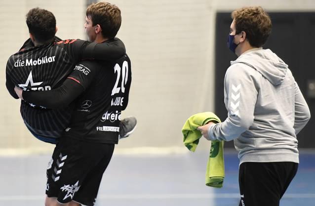 HSC-Kreisläufer Lukas Laube (M.) trägt unter den Augen von Physio Marino Schmid (r.) seinen verletzten Teamkollegen Diogo Oliveira von der Platte.