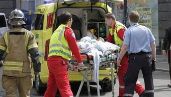 Rettungskräfte versorgen den Mann, der sich am Rande des Breivik-Prozesses selbst angezündet hat