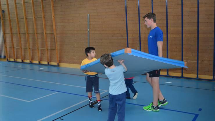 Gemeinsam anpacken: Felix Rothbrust hilft den Kindern beim Aufstellen.