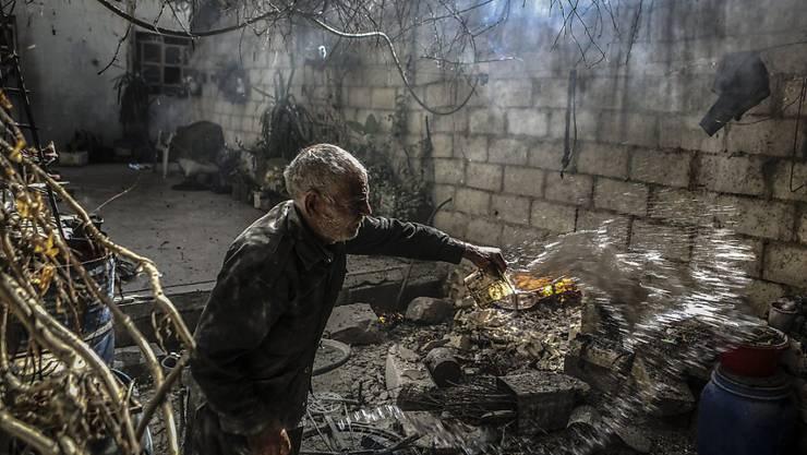 Ein Mann versucht nach Luftangriffen ein Feuer hinter seinem Haus in einem Vorort von Damaskus zu löschen. Mit Inkrafttreten der Waffenruhe soll ab Montagabend vorerst Schluss sein mit Luftangriffen.
