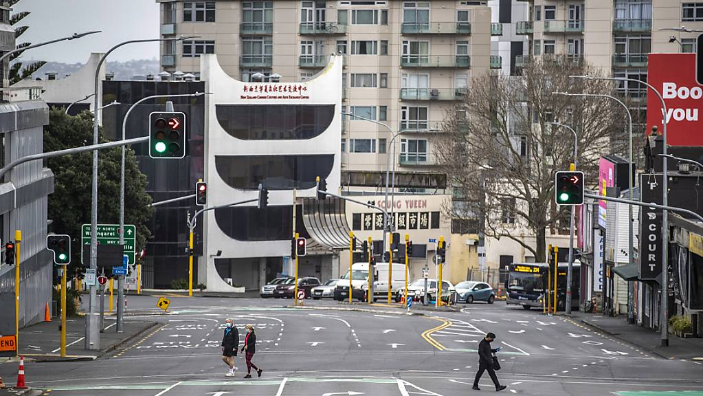 Menschen überqueren eine fast leere Straße im zentralen Geschäftsviertel von Auckland. Die Regierung von Ministerpräsidentin Jacinda Ardern gab am Montag bekannt, dass die neuseeländische Metropole eine weitere Woche im strikten Corona-Lockdown bleibt.