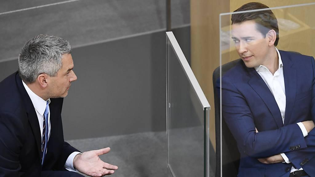Getrennt durch eine Plexiglasscheibe, spricht Innenminister Karl Nehammer (l) bei der Sitzung des Nationalrats mit Bundeskanzler Sebastian Kurz. Foto: Robert Jaeger/APA/dpa