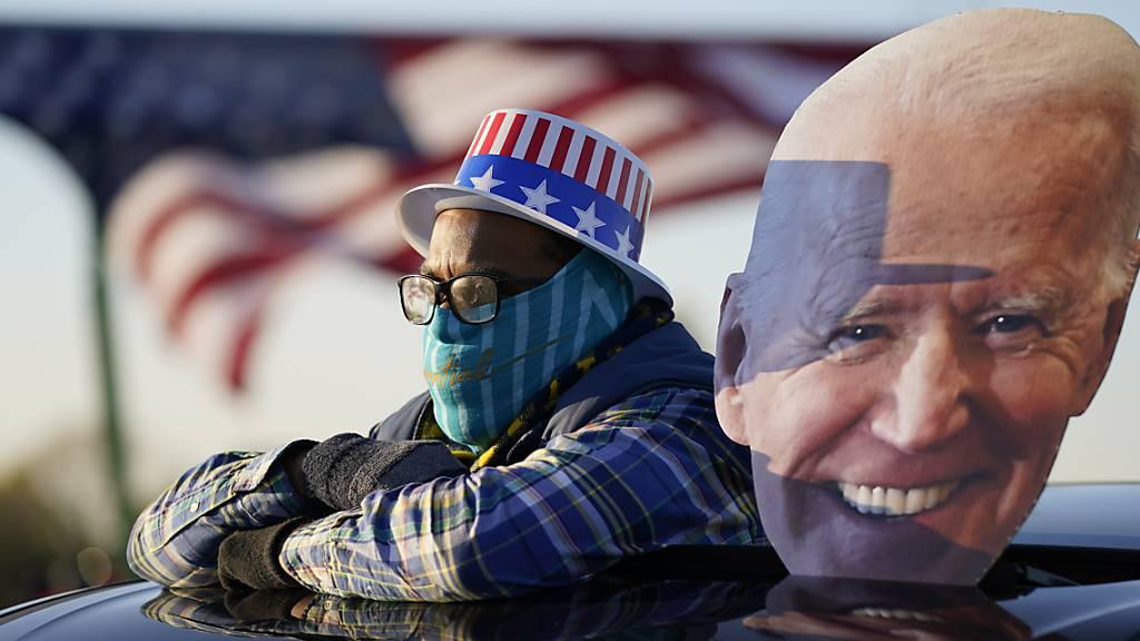 Ein Anhänger des Präsidentschaftskandidaten der Demokraten Biden schaut sich eine Wahlkampfveranstaltung von Joe Biden und und dem ehemaligen Präsidenten Barack Obama an.