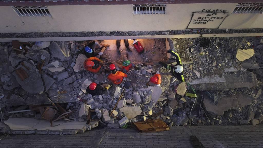 Mexikanische Feuerwehrleute arbeiten bei einem Such- und Rettungseinsatz in den Trümmern eines Gebäudes in Les Cayes. Nach dem schweren Erdbeben in Haiti ist die Zahl der Todesopfer auf 2207 gestiegen. Das teilte der Zivilschutz des Karibikstaates am Sonntag mit. Foto: Matias Delacroix/AP/dpa
