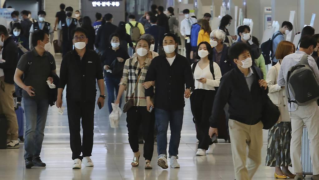 Menschen mit Mundschutz gehen am Flughafen Gimpo durch die Gänge des Inlandsterminals. Die Behörden haben alle Flugzeugpassagiere auf Grund der Corona-Pandemie zum Tragen von Gesichtsmasken aufgefordert.