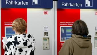 Reisende kaufen in Muenchen an einem Automaten Bahnbillets (Archiv)