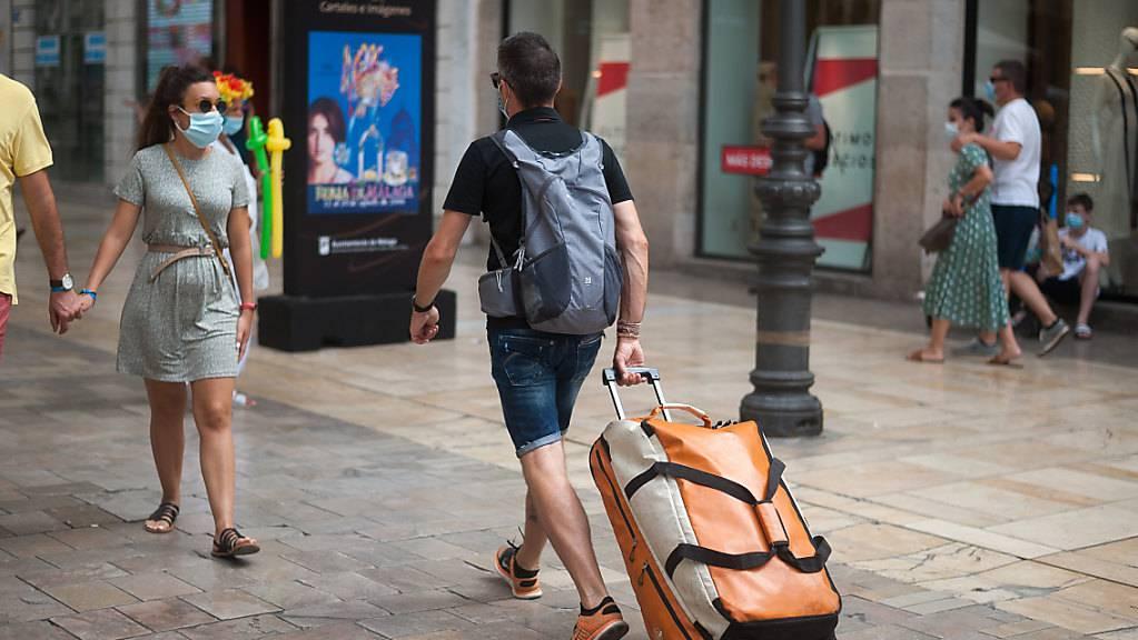 Ein Tourist trägt seine Taschen durch die Straße Marques de Larios in Malaga. Foto: Jesus Merida/SOPA Images via ZUMA Wire/dpa