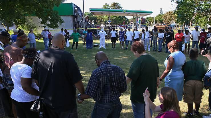 Anwohner beten nach den tödlichen Schüssen eines Polizisten auf einen Mann für Frieden.