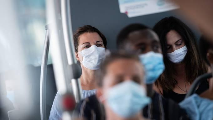 Passagiere mit Masken in einem Bus in Lugano.