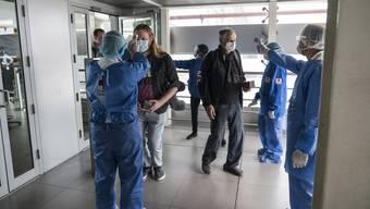 Aus Angst vor importierten Coronafällen gibt es an Pekings Flughäfen penible Kontrollen.
