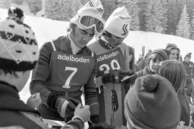 Adolf Rösti (l.) und Werner Mattle verteilen nach dem Riesenslalom am 24. Januar 1976 Autogramme.