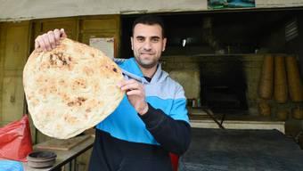 Dawod, der Bäcker, fuchtelt mit dem frisch gebackenen Taboon durch die Luft.