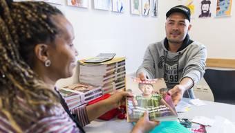 Ghulam Abass Haidari, Chef des neuen Depots in Aarau im «Offenen Pfarrhaus», übergibt «Surprise»-Verkäuferin Nasenet gegen Barzahlung zehn Magazine, die sie später vor dem Coop in Oberentfelden verkaufen wird.