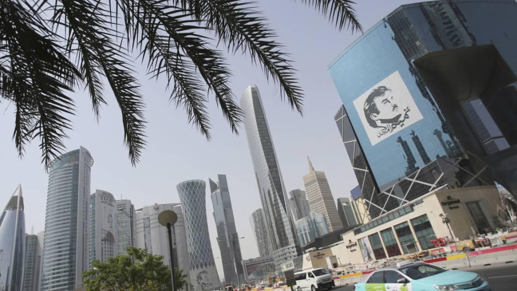 ARCHIV - Ein Taxi fährt an einem Gebäude mit einem Bild des Emirs von Katar, Sheikh Tamim bin Hamad Al Thani, vorbei. Mehr als drei Jahre nach dem Beginn einer Blockade gegen Katar legen Saudi-Arabien und seine Verbündeten ihren Streit mit dem Emirat bei. Foto: Kamran Jebreili/AP/dpa