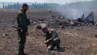 Separatisten vor Trümmern eines im Juli abgeschossenen Militärjets (Archivbild).