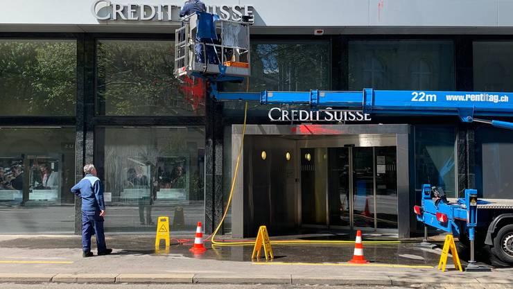 Vor der Credit Suisse ist bereits ein Reinigungsdienst damit beschäftigt, die Farbe vom Gebäude zu entfernen.