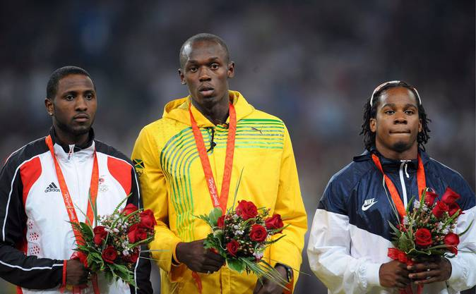 Gold medal winner Jamaica's Usain Bolt (C) is flanked by silver medalist Richard Thompson (L) of Trinidad and Tobago and bronze winner Walter Dix of the USA during the medal ceremony for the men's 100m at the Beijing 2008 Olympic