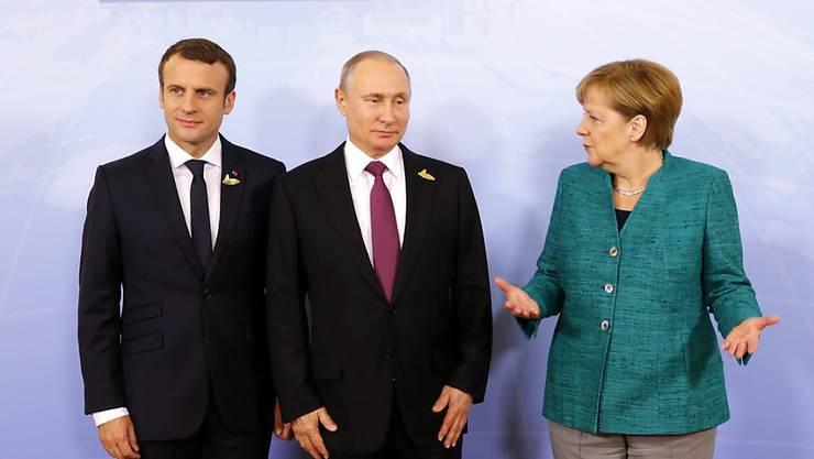 Angela Merkel und Emmanuel Macron (links) wollen mit Russlands Präsident Wladimir Putin über das weitere Vorgehen in Syrien sprechen. (Archivbild)