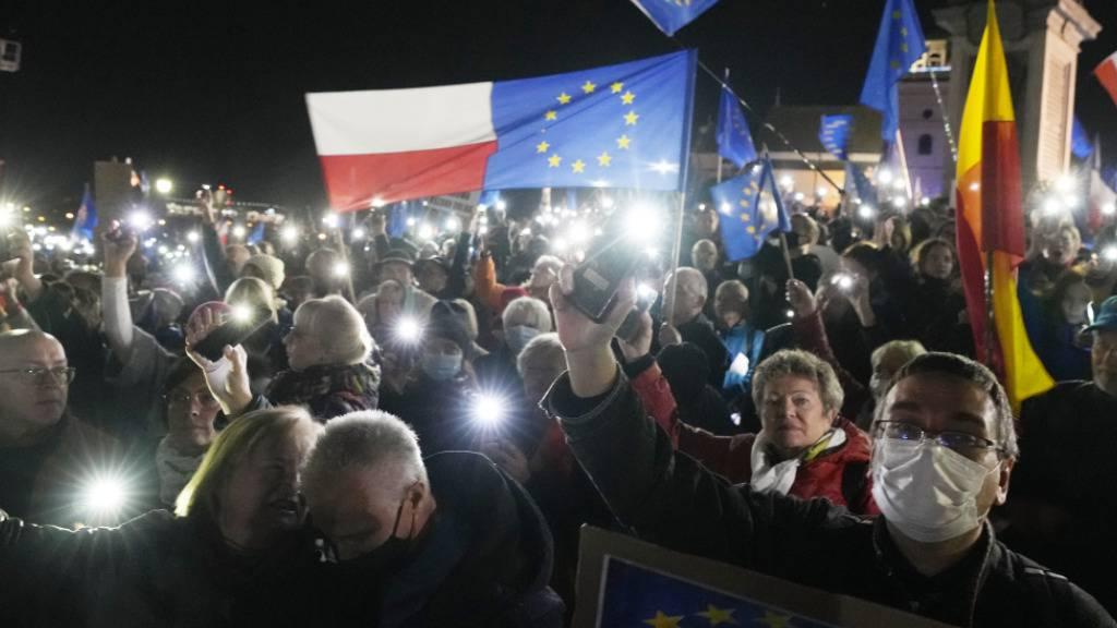 dpatopbilder - Menschen halten die Taschenlampen ihrer Mobiltelefone während einer Demonstration zur Unterstützung der polnischen EU-Mitgliedschaft in Warschau, Polen, hoch. Foto: Czarek Sokolowski/AP/dpa