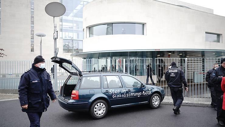 dpatopbilder - Ein Auto steht vor dem Tor des Bundeskanzleramts. Auf der Tür ist die Aufschrift «Stop der Globalisierungs-Politik» zu lesen. Foto: Michael Kappeler/dpa