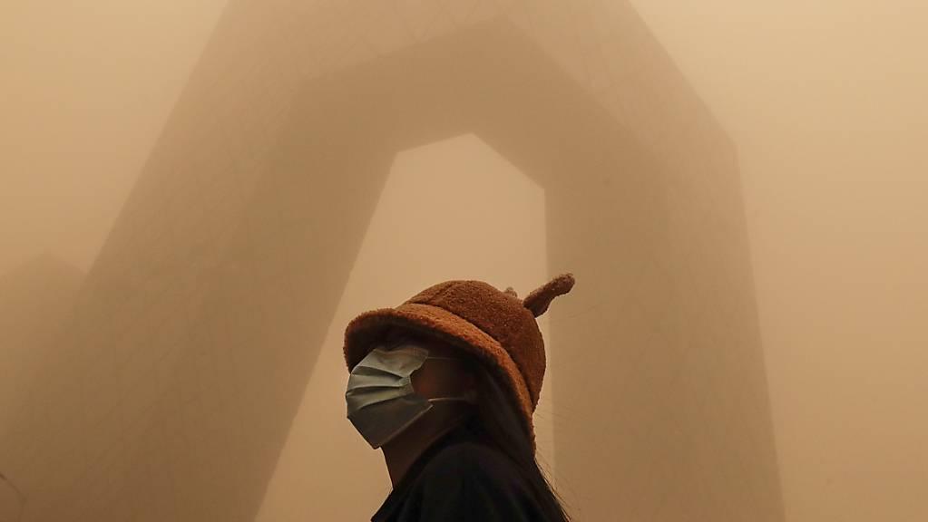 Eine Frau, die eine Gesichtsmaske trägt, steht vor dem Gebäude des China Central Television (CCTV), während die Hauptstadt von einem Sandsturm getroffen ist. Der Sandsturm hat den Himmel über Peking vernebelt und die Luftqualität ist schlecht.