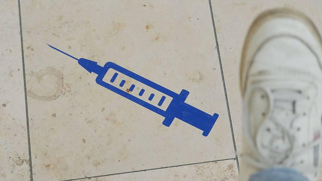 ARCHIV - Das Symbol einer Spritze ist auf dem Boden der Muldentalhalle in Sachsen aufgeklebt. Foto: Sebastian Willnow/dpa-Zentralbild/dpa