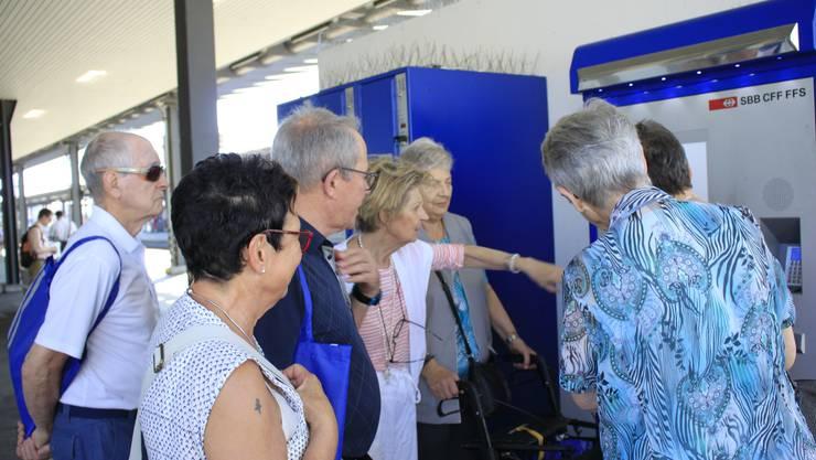 Eine Kursleiterin erklärt den Teilnehmenden die vielfältigen Bedienungsmöglichkeiten des SBB Billettautomaten