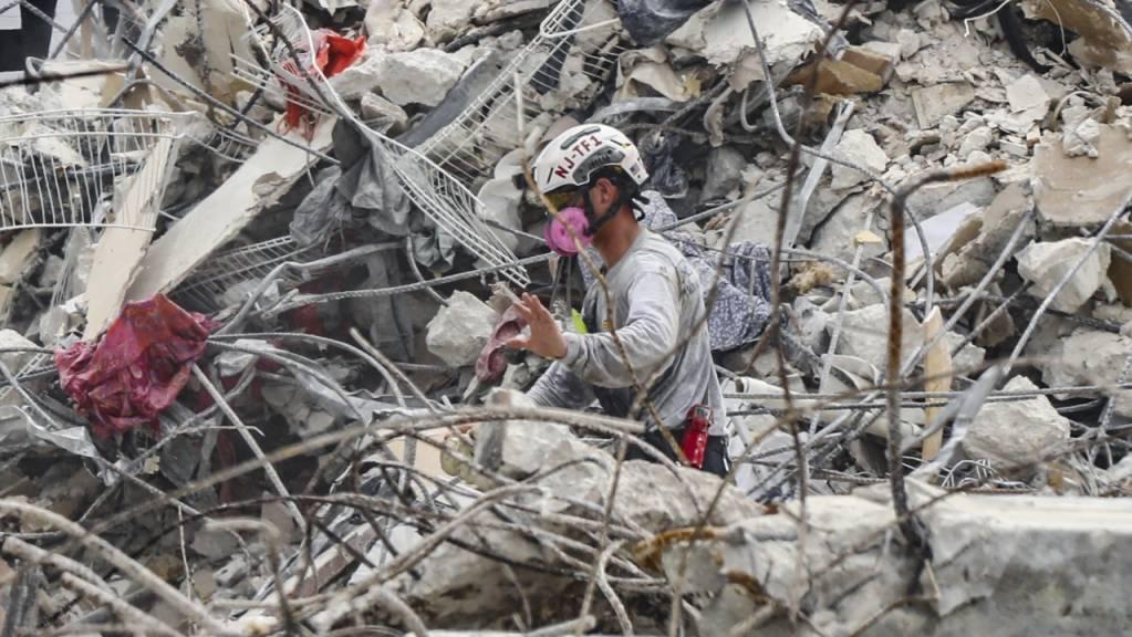 Rettungskräfte arbeiten sich durch die Trümmern des teilweise eingestürzten Wohnkomplexes.